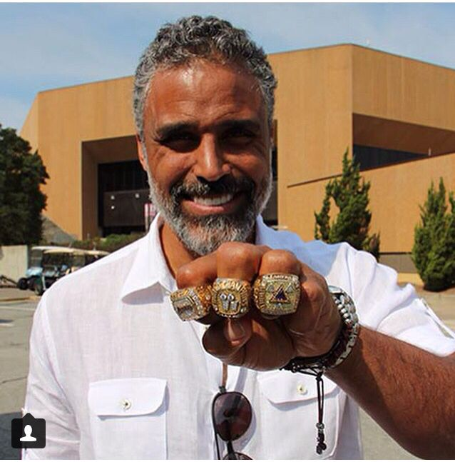 Tar Heel, Rick Fox, holds up his 3 NBA Championship rings outside of The Dean Dome