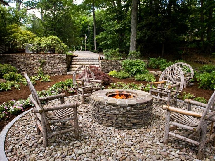 This fire pit recreates a campfire setting on a New England lakefront property designed by YardApes, based in Connecticut. The stacked stone, pebble floor and handiwork in the design of the wooden chairs creates an inviting entertaining spot.