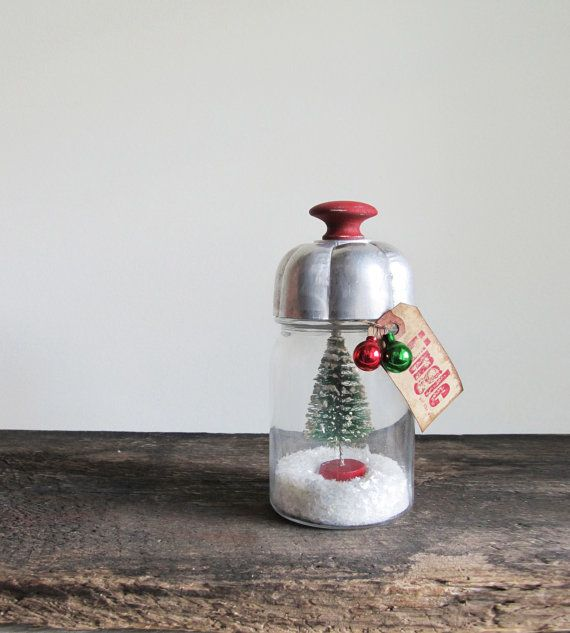 An adorable snow globe (liquid-free) made with a pint jar, mica flakes plus vintage finds, including a bottle brush tree, tart tin and miniature feather tree, glass ornaments. A wood knob was attached to the vintage jello mold, mica flakes fill the bottom of the jar and the neck is adorned with a tea-stained tag rubber stamped with Jingle all the way.