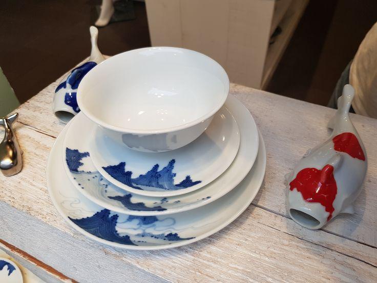 Weiß-blaues Porzellan mit kunstvoller Landschaft.
