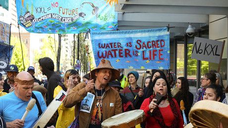 Native American leaders and climate activists join together in song outside of a Chase Bank location, to oppose the Keystone XL pipeline, in Seattle, Washington. ©Reuters