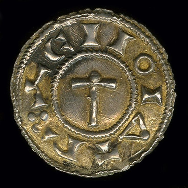 """A Viking penny with an image of Thor's hammer with a """"Hand of God"""" resting on top on the reverse, and a drawn bow and arrow (possibly a misrepresentation of a ship) on the front. Cast out of silver. Made in 920 at the mint of Regnald, the Viking king at York. Currently held at the British Museum"""