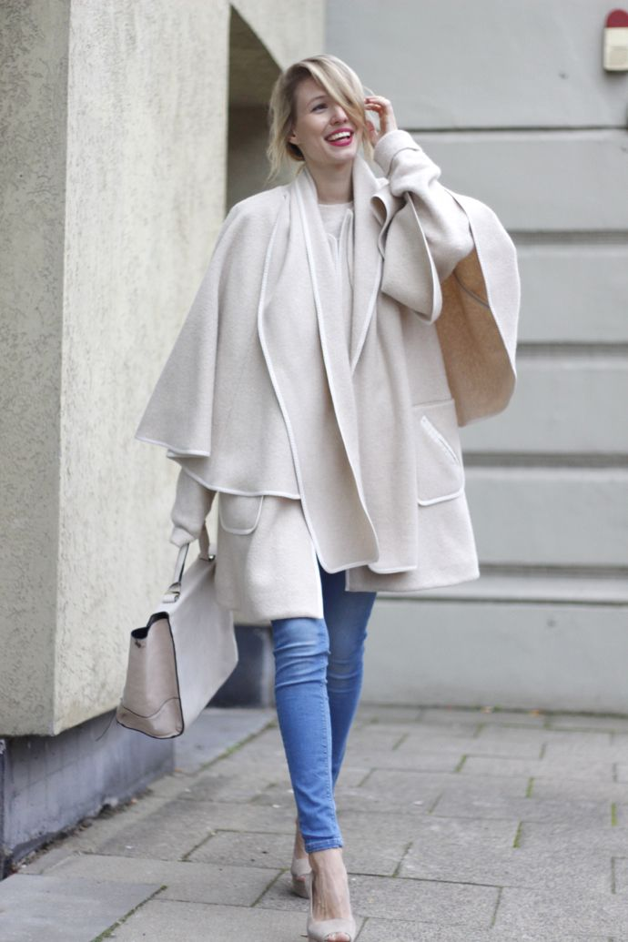 @ohhcouture sports a light beige sleeveless coat with attached cape & scarf…