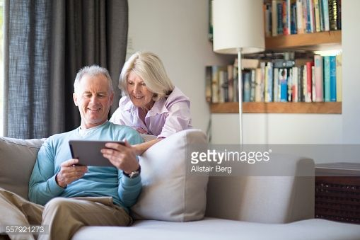 Stock Photo : Senior couple using tablet computer at home