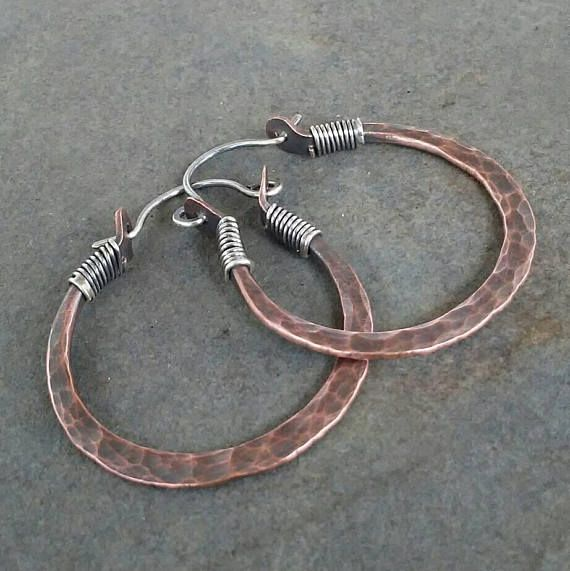 I made this pair of hoop earrings by hand using sterling silver and copper. They measure 1 1/2 inches in length from the top of the ear wire to the bottom of the hoop and 1 3/16 inches in width. They have been oxidized to show detail and add rustic country charm.