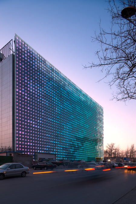 The Xicui Entertainment Complex in Beijing, China. The glass curtain wall contains photovoltaic systems which collect solar energy during the day and use it to power an LED display at night. By Simone Giostra & Partners.