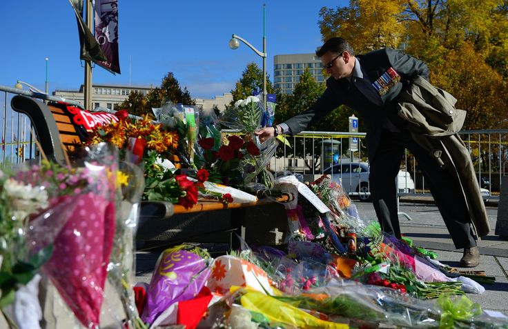 A Canadian Armed Forces veteran pays tribute to Corporal Nathan Cirillo in front of the National War Memorial during a Commemoration event in Ottawa, Ontario on October 23, 2014.