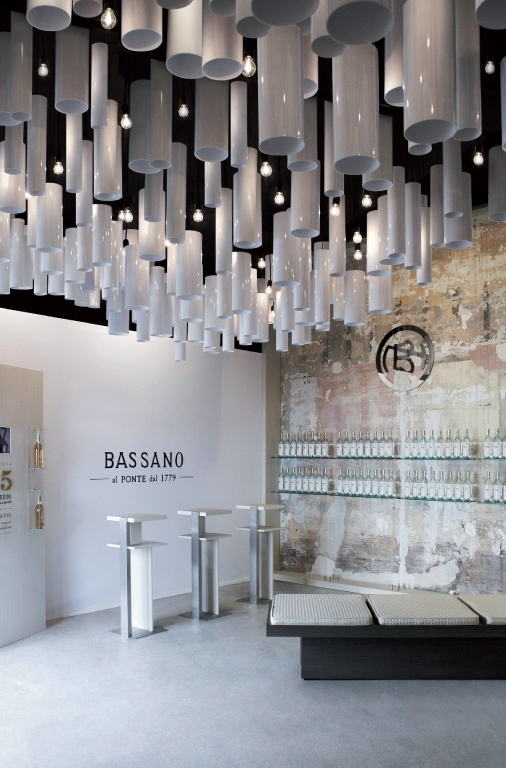 "Temporary Space Nardini. White walls, an installation of cylinders in shiny paint, everything to remember the famous bordolesi bottles of the ""Bianca."""
