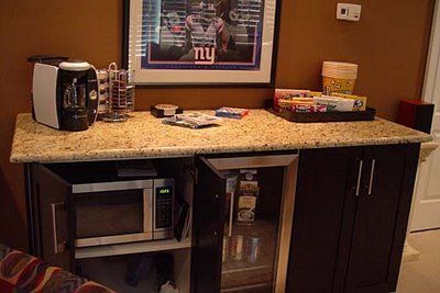 """The snack bar is 2 IKEA kitchen cabinets and a 15"""" beverage cooler.  Microwave for movie popcorn. Cabinet on right conceals a trash/recycling center, & storage. A granite remnant forms the countertop. Three puck lights above are controlled by Z-wave technology with a Harmony 890 universal remote, as is all lighting in the space. This is a retrofit anyone can do."""