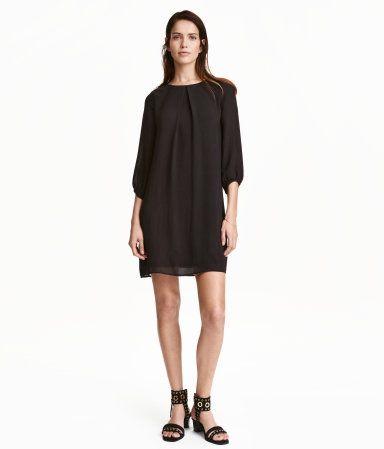Lige skåret kjole i chiffon. Kjolen har wienerlæg foran og trekvartlange ærmer. Synlig lynlås i nakken. Foret med jersey.