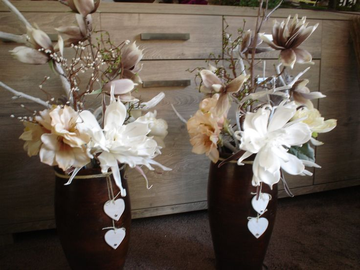 hoge pot met bloemen en takken, een paar hartjes maken het af.