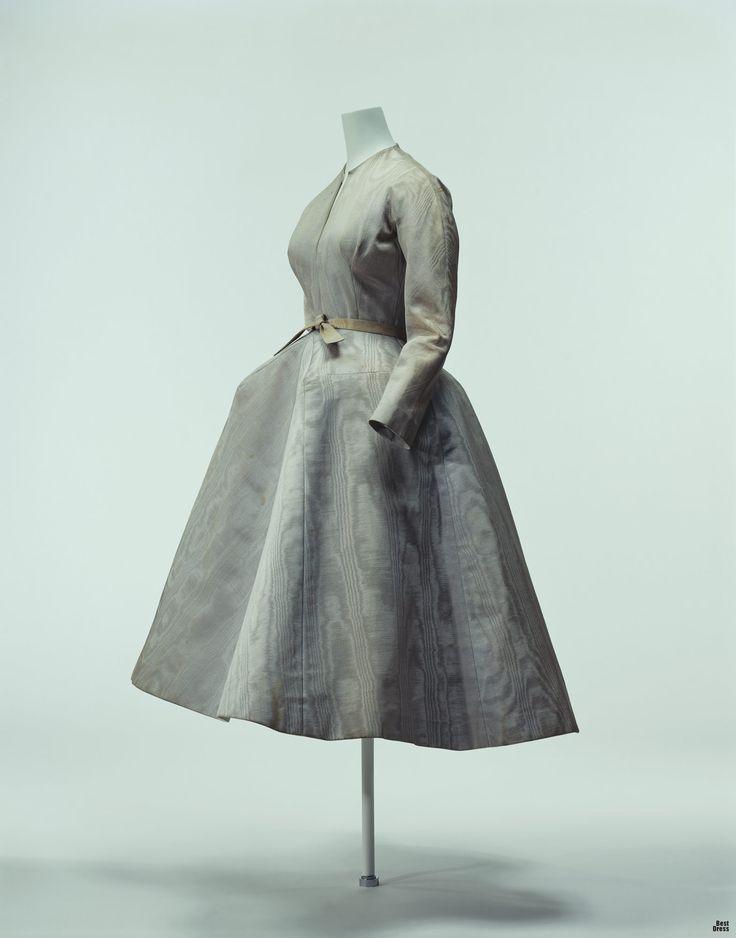 """Платье из коллекции """"Profile Line"""", которая имеет характерный резкий силуэт. В отличие от облегающей верхней части, широкая юбка выполнена как бы в трех измерениях. Верхнюю юбку поддерживает жесткотканная нижняя юбка, которая и придает такой идеальный трехмерный силуэт."""