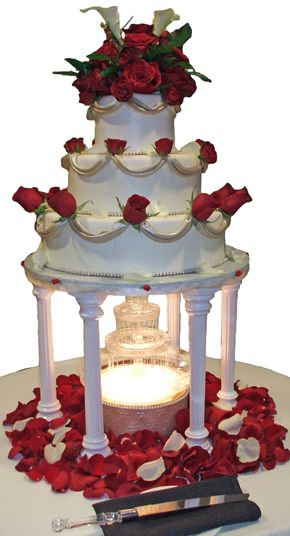 3  tier ivory wedding cake with champagne fondant decorations and fresh red roses on a lighted water fountain