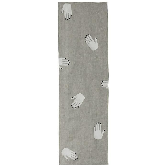Oatmeal linen table runner with white hands and black nails