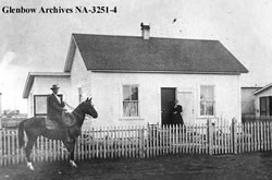 Grandpa on horse in front of pioneer house