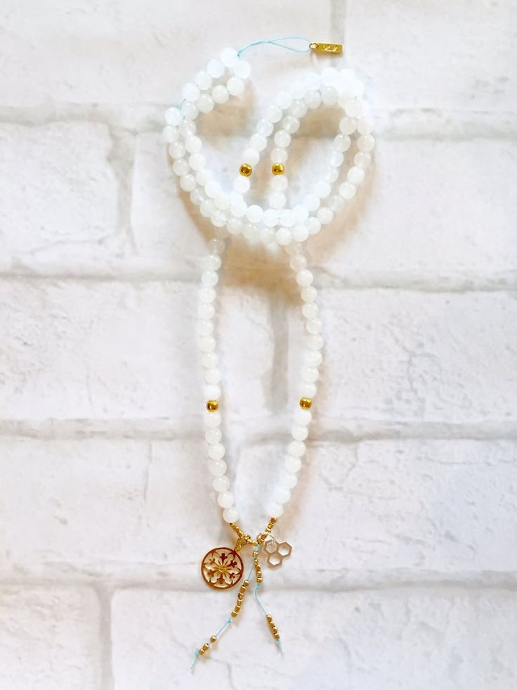 White Jade Mala Necklace Intentional jewelry made with white jade gemstones and sacred geometry pendents. Used during meditation, yoga practice or simply worn as a beautiful piece of jewelry. Each gemstone hold unique healing properties and can be used as a daily reminder of your positive intentions.