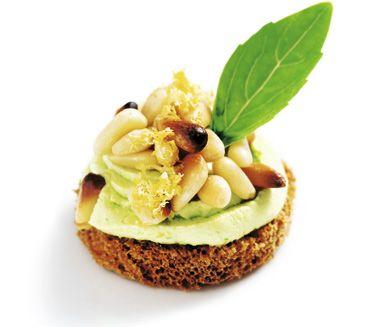 Kanapé med ostkräm och pinjenötter är en perfekt liten aptitretare som går snabbt att tillaga. Den lena dessertosten mixas med basilika och citron innan den spritsas ut på rundlar av bröd. Strö sedan över rostade nötter och eventuellt flingsalt.