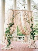 Draped blush wedding arch with ivy