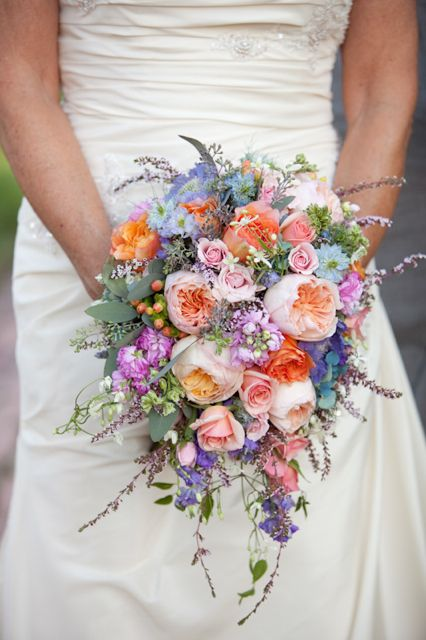 A cascading bouquet of peach juliet cabbage roses, pink spray roses, free spirit roses, lavender stock, blue nigella, calcynia heather, veronica, and seeded euc. Photography by Tracy Timmester.