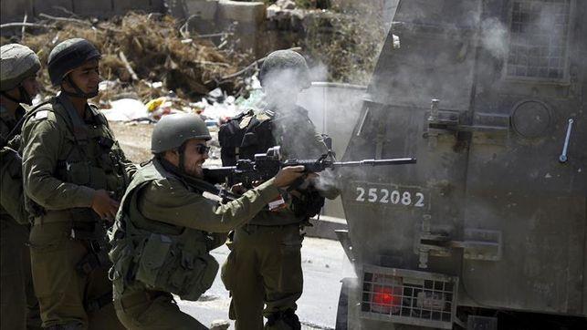 El ejército israelí se enfrenta enfrenta a varios palestinos durante los disturbios desatados en la localidad cisjordana de Hebrón ayer tras tras el asesinato de un bebé quemado vivo y las heridas graves a sus padres y hermano en un ataque de supuestos extremistas colonos en la localidad de Duma. EFE
