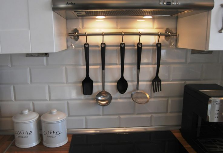 Biała kuchnia z płytkami w kształcie cegieł.   White kitchen with plate-shaped bricks, white coffee container