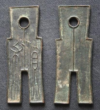 The front and reverse sides of a spade-shaped metal coin, issued during the reign of Wang Mang (r. 9–23 CE) of the brief Xin Dynasty of China.