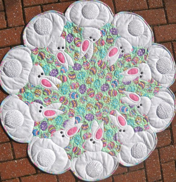 "~40"" diameter. Ten sweet bunnies show off their tails which use chenille fabric 'you' make. Stacked appliqué is completed while quilting to make this a quick"