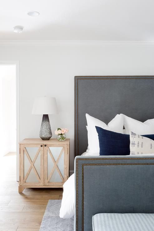 A Gray Velvet Bed With Footboard And Tall Headboard Accented Br Trim Is