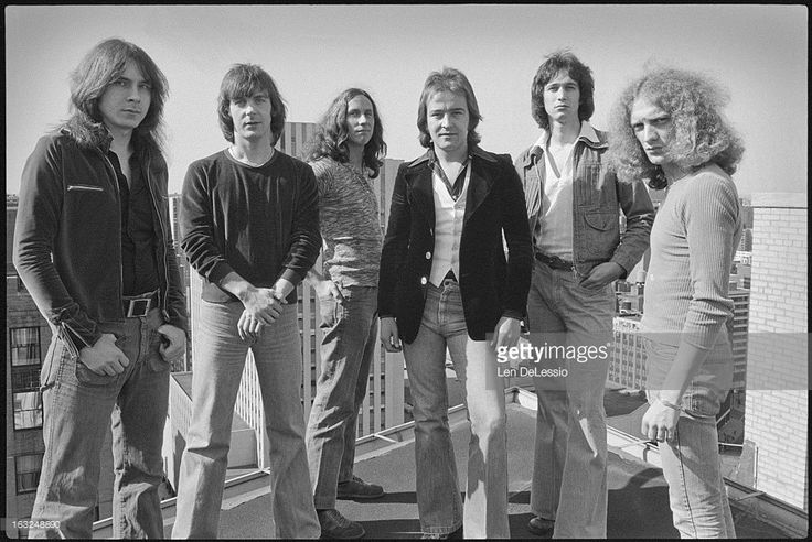 Group portrait of the British & American rock band Foreigner as they pose together on a rooftop, New York, New York, 1976. Pictured are, from left, American musician Al Greenwood, British musicians Ian McDonald, Dennis Elliott, and Mick Jones, and American musicians Ed Gagliardi and Lou Gramm.