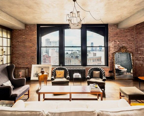 Kirsten Dunst's NYC living room has an elegant, gothic touch with black leather chairs and exposed brick walls