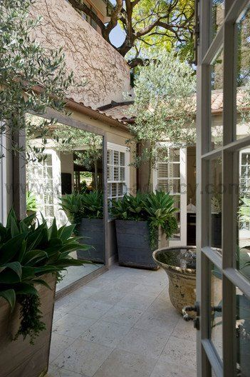 add a mirror to a small court yard to give the illusion of more space