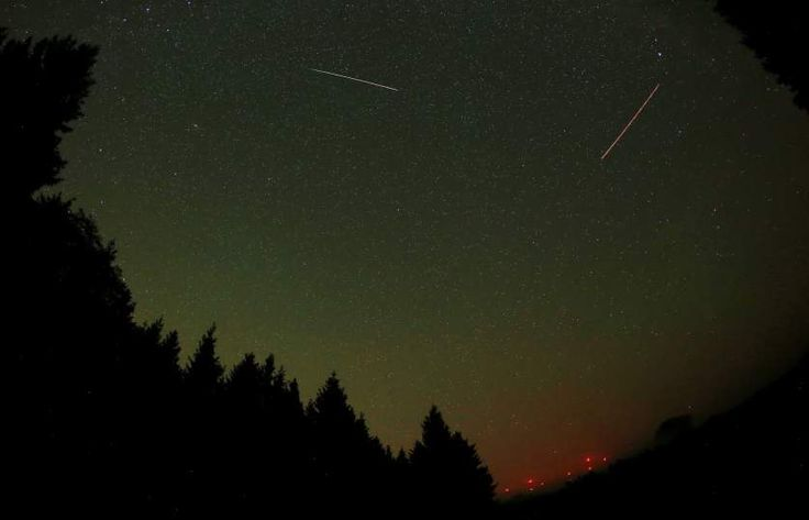 A meteor from the Perseid meteor shower (left) and the lights from a plane (right) streak across the sky near Gemuend, Germany on Aug. 13, 2015.