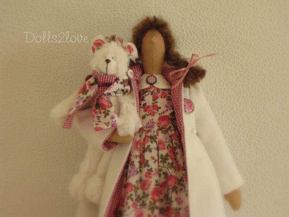 Tilda doll Abigail wearing a liberty fabric dress, an off white wintercoat accompanied by her little teddy bear.