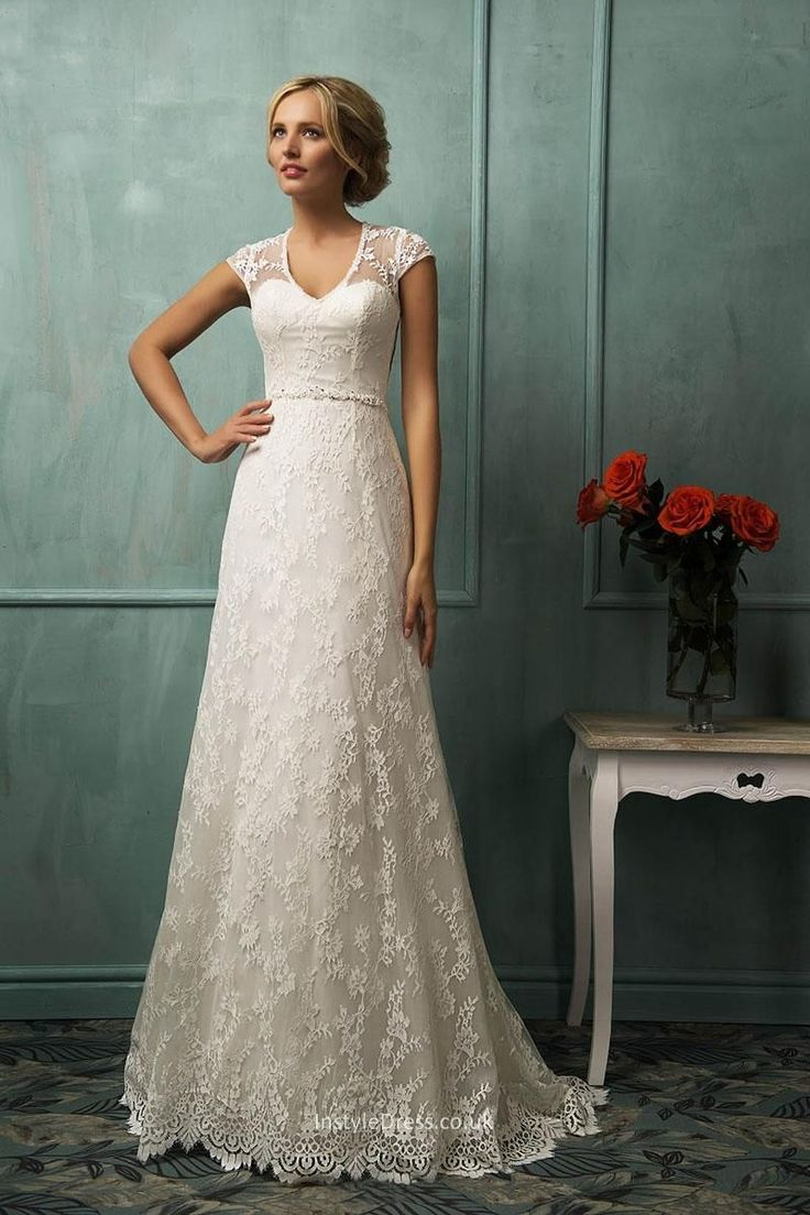 It's an vintage wedding dress which with long tail. Cap sleeves on the bodice and lace overlay covered on the tulle skirt make it comes into a-line silhouette. Matching with sash.
