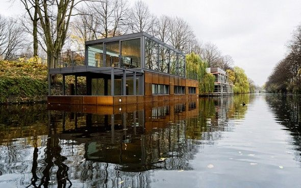 """Houseboat on the Eilbek Canal  In what appears to be the floating contemporary housing district of Hamburg Germany, sits the aptly named """"House on the Eilbek Canal"""" which was designed by Sprenger von der Lippe. The two level, 1506 square foot residence strikes a unique balance between its natural surroundings and a modern urban aesthetic."""