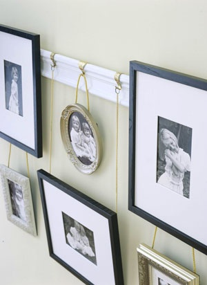 It's like a photo album for your wall! A piece of common molding to make a picture rail. Decorative golden picture hooks fitted with short lengths of hardware-store chain suspend all sizes and shapes of frames. Simply cut the chain to the desired length and top with a circular link. Then hang each piece and enjoy .