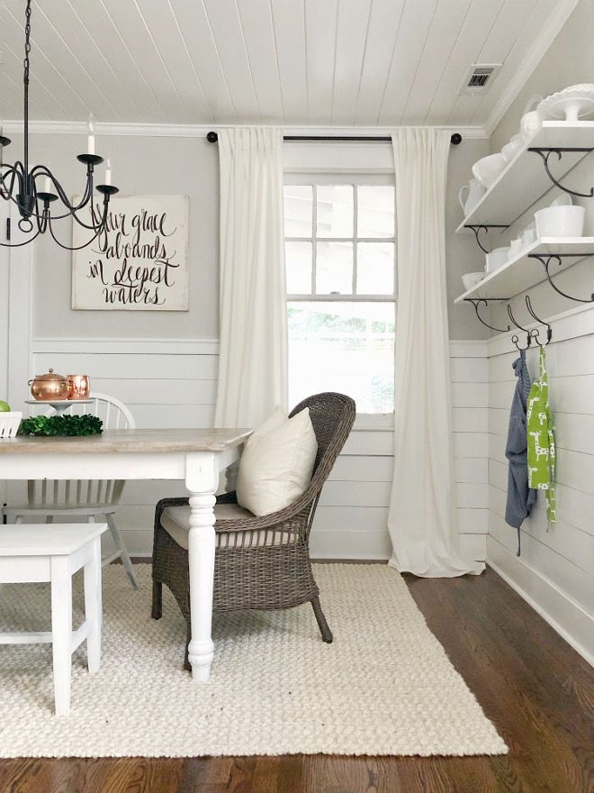 Farmhouse dining room rug, hardwood floors, walls shelves, half wall shiplap and neutral paint color. Home Bunch blog