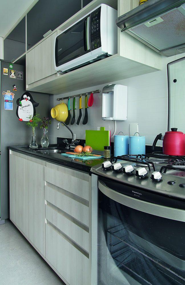 Apenas um lado da cozinha recebeu marcenaria, tendo em vista a melhor área de circulação. As portas dos módulos superiores, de vidro preto, dão charme aos móveis de madeira clarinha.