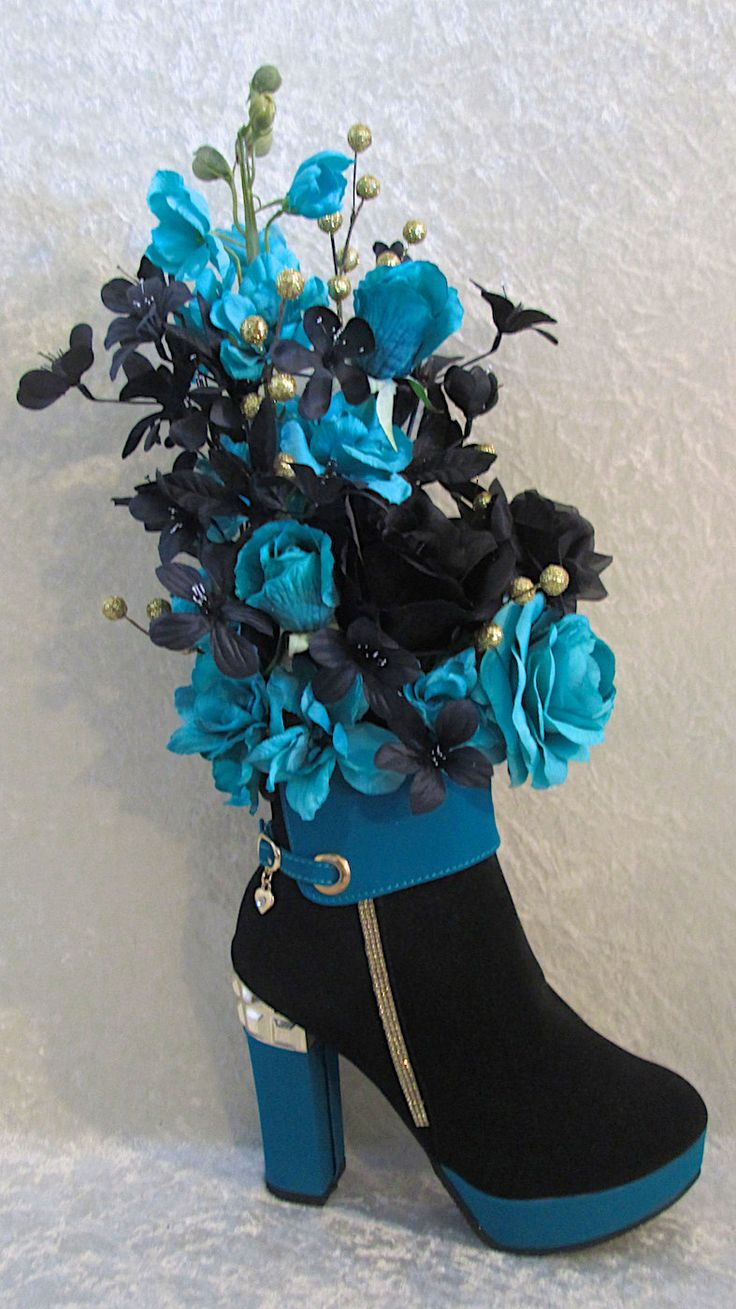 Beauty in a Shoe!! This very Unique floral arrangement is made in a real Turquoise and Black Suede High Heel Ankle Boot. The boot has a row of pretty little rhinestones down the side and a tiny heart pendant hanging off the buckle. The flowers include Black and Turquoise Roses with Delphiniums, Azaleas and Glittery Gold Balls. This arrangement is Beauty, Elegance and Fun all wrapped in one.  The completed arrangement measures approx. 15 inches tall by 10 inches wide by 8 inches deep. Photo…