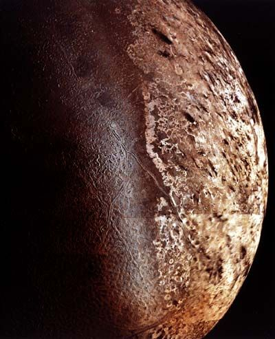 Triton taken in 1989 by Voyager 2. Fascinating terrain, a thin atmosphere, and even evidence for ice volcanoes on this world of peculiar orbit and spin.