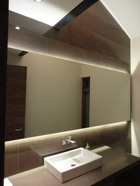Backlit Mirror Powder Room - LED Strip (or Panel) Lights  Strips backlight this mirror above and below, creating a soft but dramatic look. Because of an additional covering, strip lights are moisture resistant, which makes them a great choice for lighting a bathroom vanity. - 186 Lighting Design Group - Gregg Mackell