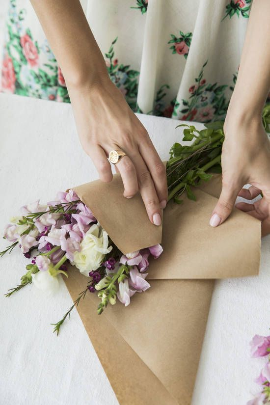Wrap some inexpensive flowers in craft paper. Fill up a basket and pass them around to people you see. This project is supposed to be fun, affordable and doable for all!    florals by: yasmine floral design  photography by: julia stotz