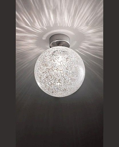 The Rina FA 16 wall or ceiling light by Vistosi has been designed by Barbara Maggiolo. The Rina FA 16 wall or ceiling light is part of a collection with diffuser in gloss blown glass. This beautiful light fixture has a decoration realized with the insertion of particular white murrhines which do not dilate so much during the blowing phase. Inspired by the dandelion flower and using the traditional murrina technique that creates an organic light texture, Rina is avail...