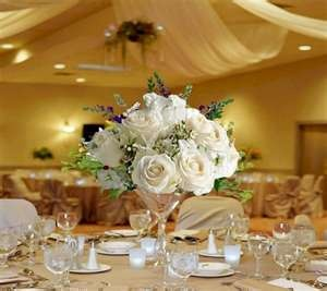 A medium height centerpiece that also incorporates white, with some lavender peeking through. Not a fan of the martini glass, but nice arrangement of colors and height.