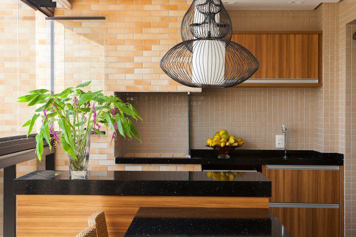 Esta varanda gourmet tem estilo rústico pelo uso da madeira clara e bancada em granito e tijolinhos foscos contrastando com o brilho das pastilhas. Projeto da arquiteta Eliana de Souza.