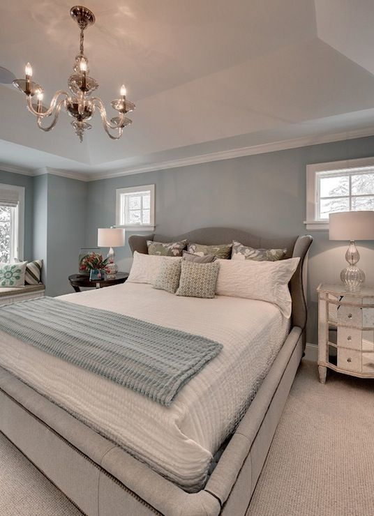 Gray and blue bedroom with blue walls framing gray camelback velvet bed filled with soft white bedding, gray and green floral pillows and blue throw blanket. Mismatched nightstands with mercury glass lamps flank gray wingback headboard. Master bedroom features built-in window seat and tray ceiling with gray glass chandelier over bed.