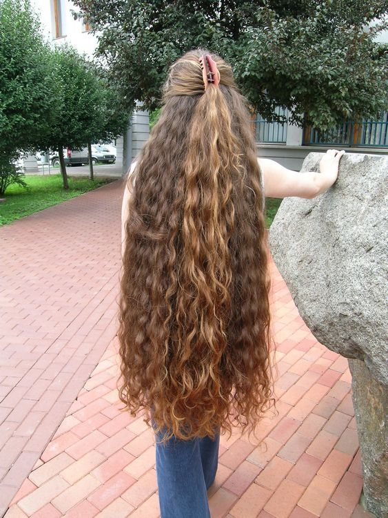 Simply gorgeous. Her wavy hair is very long and thick. It's knee length and an ultra dark shade of musty blonde.