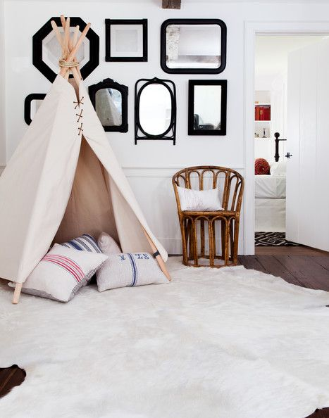 Country Doors - A tepee filled with pillows atop a hide rug