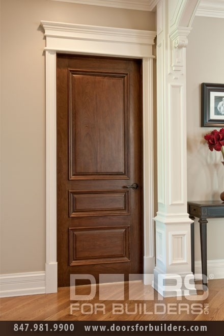 White molding around a wood stained door-