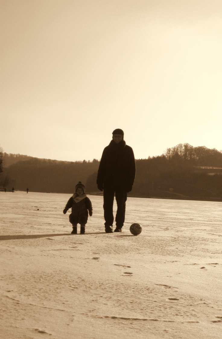 father and daughter on a frozen lake in february